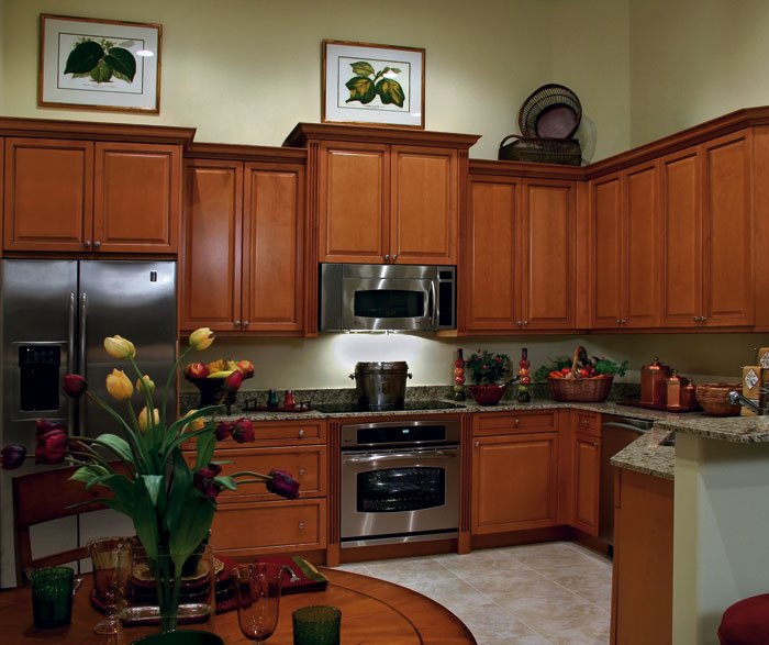 Maple kitchen cabinets in medium brown finish by Kitchen Craft Cabinetry